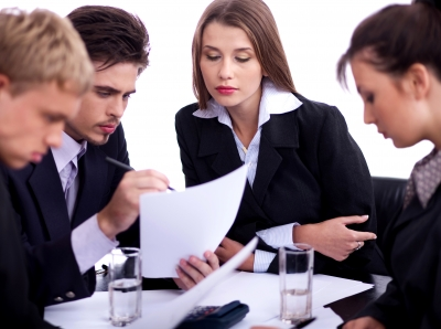 Young professionals business people discussing seriously in their meeting with documents over white background.