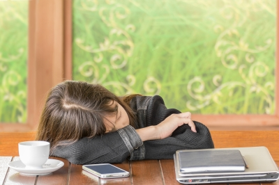 Asian Girl Sleeping While Sitting At Desk Stock Photo